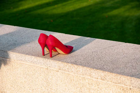 Red high heels shoes standing on a granite curb Foto de archivo