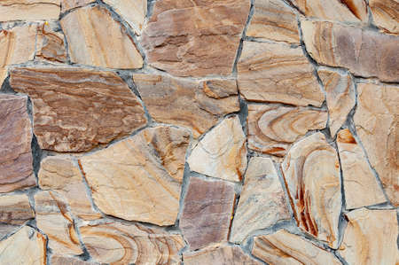 Rainbow Sandstone. Clastic sedimentary rock composed mainly of sand-sized silicate grains. Stone wall. Background. Close up. sandstone is composed of quartz or feldspar