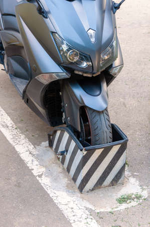 Motorcycle, Motorbike Front Wheel Chock Parking Rack. Lockable Motorcycle Scooter Receipt and Permit Holders Stock Photo
