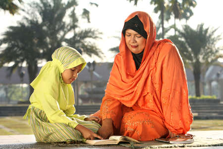 Muslim Mother and Child  Reading Koran Stock Photo