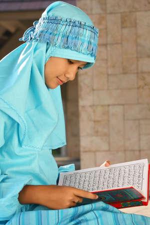 jilbab: Muslim Girl Reading Quran  Stock Photo