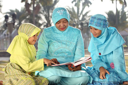 Muslim Mother and Kids Reading Quran