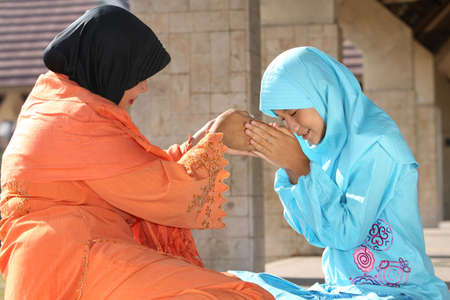 Muslim Mother and Child Holding Hands