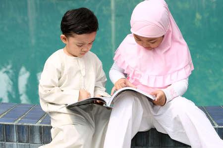 petite fille musulmane: Les enfants musulmans de lecture d'un livre Banque d'images