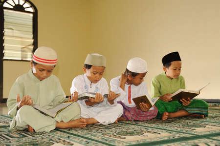 kids reading: Muslim Kids Reading Koran Stock Photo