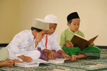 Muslim Kids Reading Koran Stock Photo