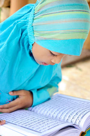 indonesia girl: Muslim Girl Reading Koran Stock Photo