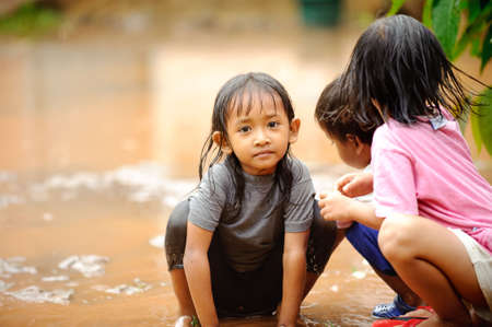 Poverty children playing in a rain