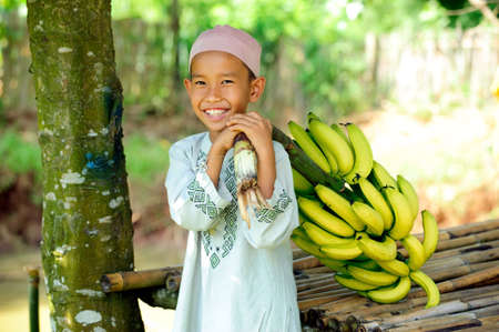 Child holding bunch of bananas