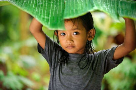 indonesia people: Child  hiding from rain