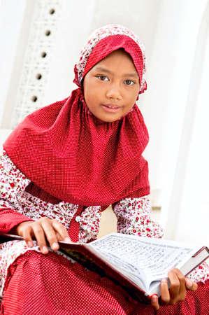 Child holding Koran photo