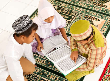 Smal group of children reading Koran Stock Photo