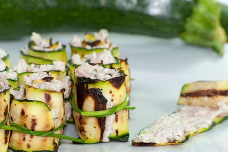 filled roll: Grilled zucchini rolled with cream cheese in a white plate