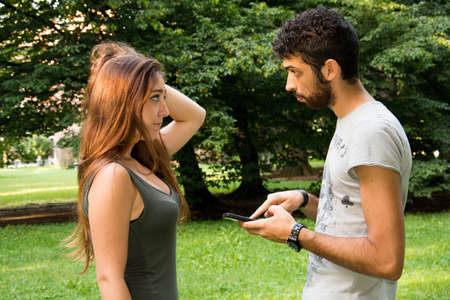 A dubious boy with a smartphone and her girlfriend in a city park