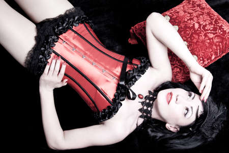 burlesque: Woman in a corset lying on a bed Stock Photo