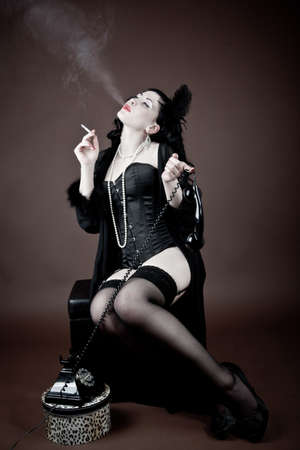 Bored woman smoking a cigarette during a telephone call  vintage