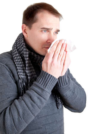 Man with a cold sneezing into a tissue  Stock Photo