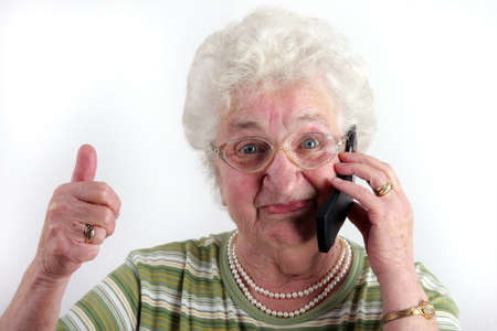 old cell phone: A old lady using a mobile phone