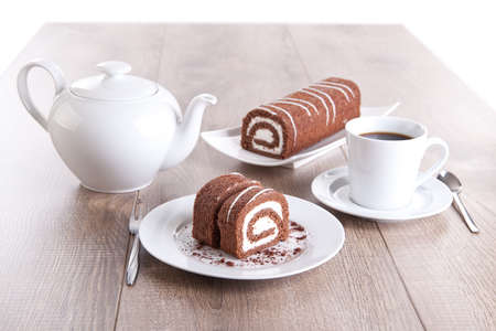 Chocolate roll with a cup of coffee / tea and a pot Stock Photo - 16480838