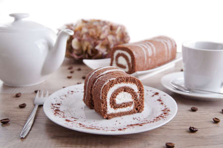 Chocolate roll with a cup of coffee / tea and a pot Stock Photo - 16480848