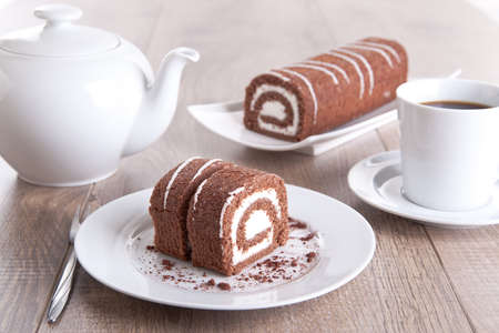 Chocolate roll with a cup of coffee / tea and a pot Stock Photo - 16480846