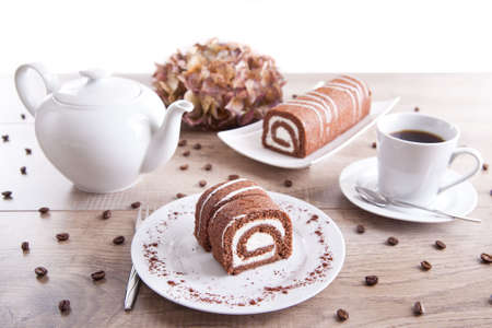 Chocolate roll with a cup of coffee  tea and a pot photo