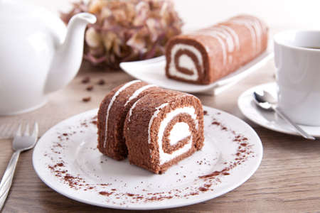 Chocolate roll with a cup of coffee  tea and a pot