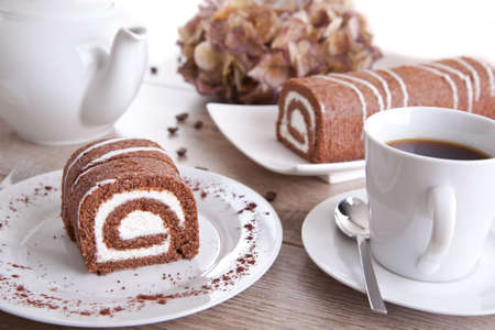 Chocolate roll with a cup of coffee and a pot photo