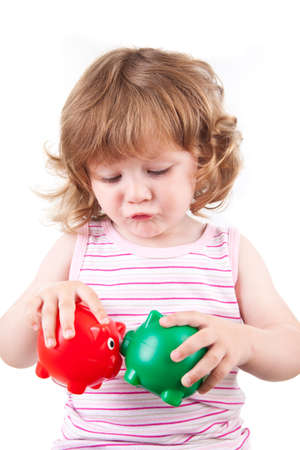 Little girl play with two piggy boxes Stock Photo