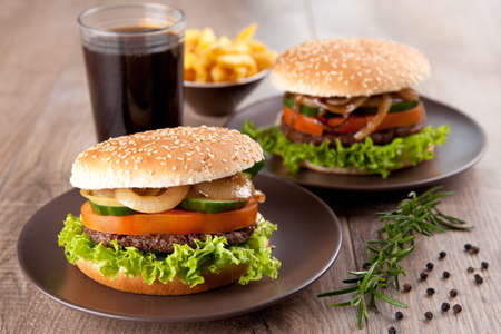 food and drink: Two hamburgers with potato chips and drink Stock Photo