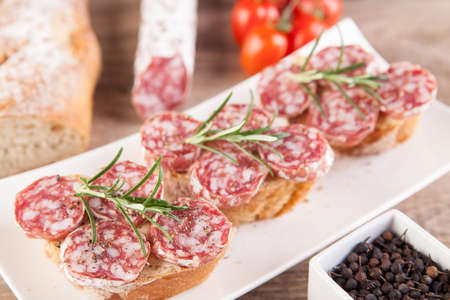 Bread with sliced salami and rosemary Stock Photo