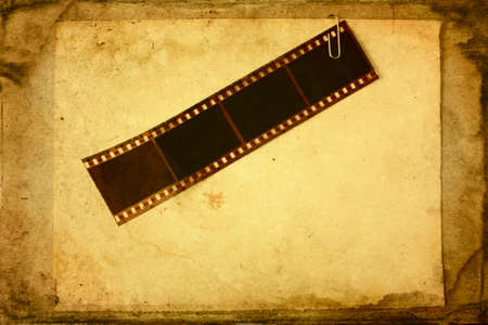 Film tape attached to the paper in grunge style photo
