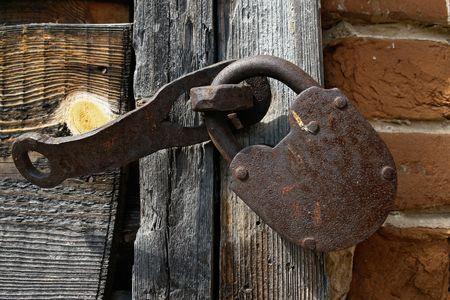 Old handmade padlock on the wooden door                                photo