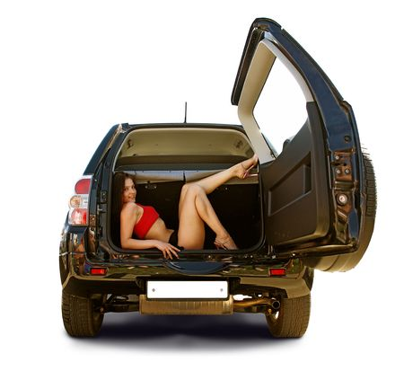Yong girl laying in a trunk. Isolated on white. Stock Photo