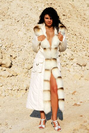 Girl in furs on the rocky background. photo