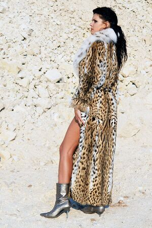 Girl in fur coat on the sky background. photo
