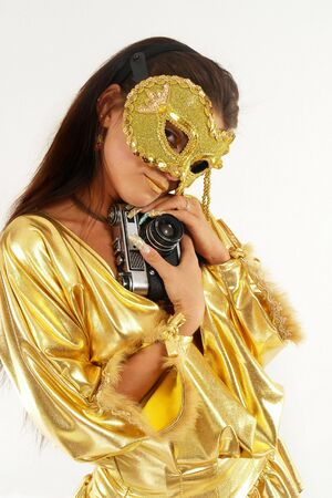 Sexy smiling girl in golden mask & dress with old photo camera. photo