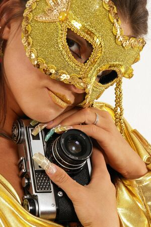 Sexy smiling girl in golden mask with old photo camera. photo