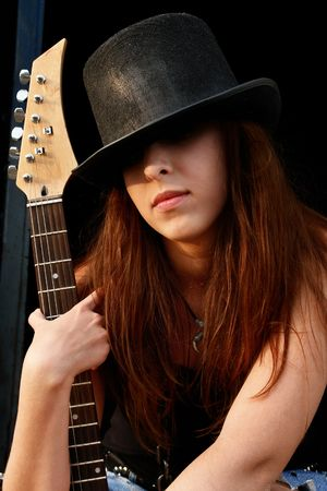 Portrait of pretty red-haired girl with electric guitar in a black hat. photo