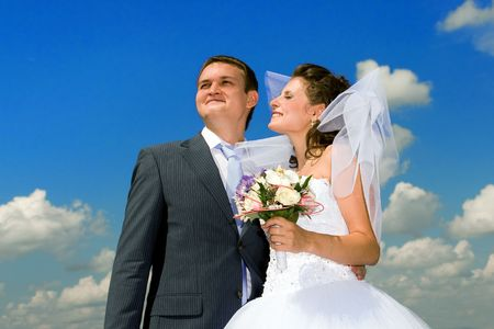 Groom with the bride on the cloudy sky background. photo