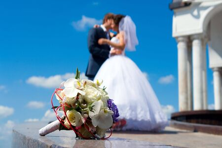 Brides bouquet on the marble. Kissing couple on the background. photo