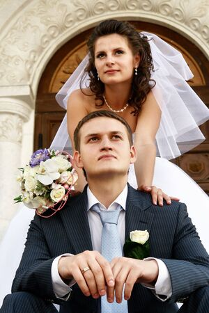 Groom is sitting near the church and thinking about future. His bride with the flowers near him. photo
