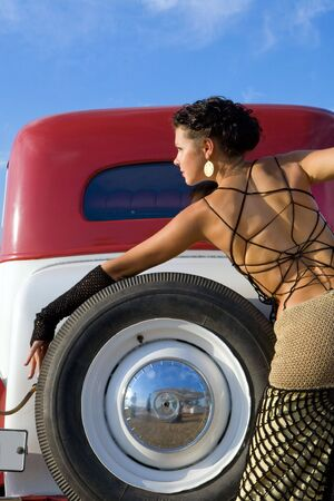 Pretty girl in exclusive woolen dress near the vintage car. photo