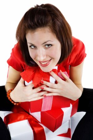 expressing: Pretty girl in red dress is holding  presents. Isolated on white.