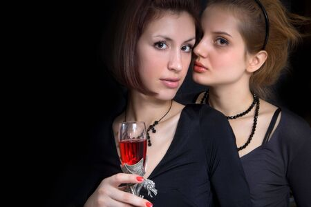 Two pretty girls with the wineglass of red wine. photo