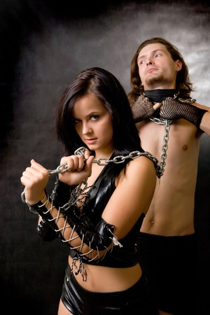 Pretty woman in leather clothing is holding a wired slave.