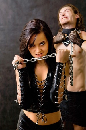 Pretty woman in leather clothing is holding a wired slave. Stock Photo - 4100129