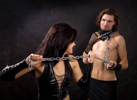 Pretty woman in leather clothing is holding a wired slave. Stock Photo