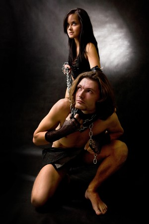 Pretty woman in leather clothing is holding a wired slave. photo
