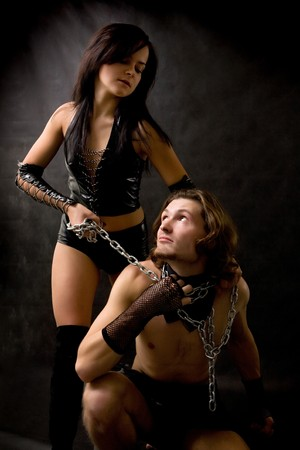 Pretty woman in leather clothing is holding a wired slave. Stock Photo - 4100124